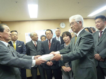 宇都宮市選挙管理委員長に署名簿を渡す上田憲一代表(右)と阻止する会役員