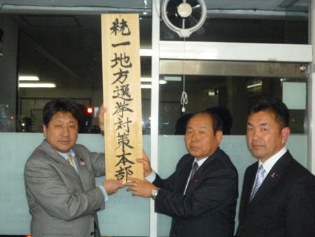 看板を設置する(左から)田城副代表、福田代表、松井幹事長